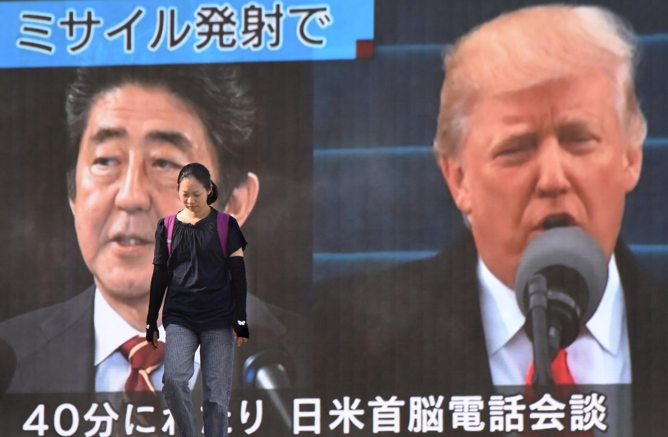 De Japanse premier Shinzo Abe en de Amerikaanse president Donald Trump op een reuzenscherm in Tokio. Japan en de VS verzochten de VN Veiligheidsraad om een spoedzitting.