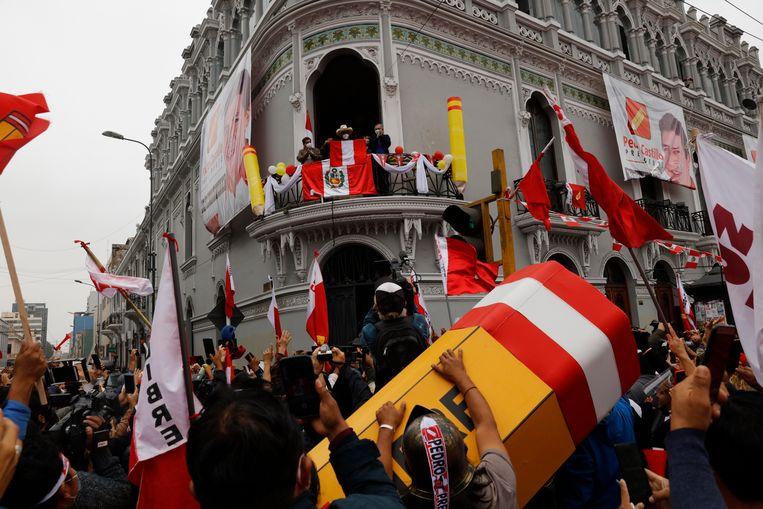 Presidentskandidaat Pedro Castillo kijkt uit over supporters vanaf het balkon van zijn campagnehoofdkwartier terwijl ze de gedeeltelijke resultaten vieren in Lima, Peru, maandag 7 juni 2021, de dag na de tweede ronde. Met stemmen van landelijke gebieden en Peruaanse ambassades in het buitenland vanaf donderdag 11 juni, behield de linkse Pedro Castillo zijn smalle voorsprong, met 50,2% van de stemmen tegen 49,8% voor de conservatieve Keiko Fujimori.  Beeld AP