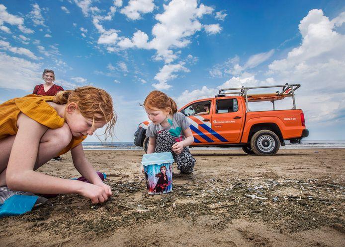 Vrijwilligers van de Haagse Vrijwillige Reddingsbrigade bewaken het strand vanuit de auto. Rowena (L) en Britney zijn met hun moeder Katinka uit Arnhem gekomen om van de zee en het strand te genieten.