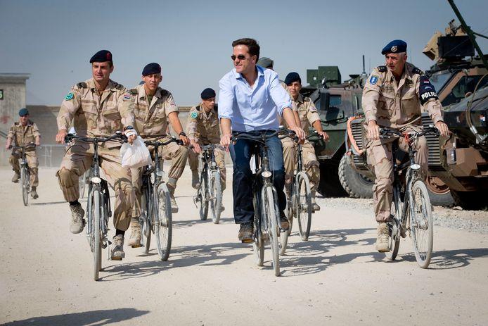 Minister-president Mark Rutte fietst in 2013 samen met militairen over Kamp Kunduz tijdens zijn bezoek aan de manschappen in Afghanistan.