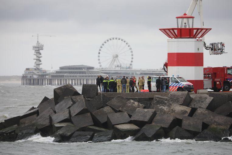 Met behulp van een hoogwerker wordt een stoffelijk overschot dat vandaag bij het Noordelijk Havenhoofd in Scheveningen geborgen. Beeld Regio15