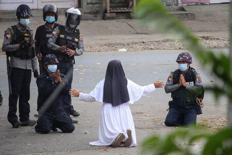 Een non in Myanmar smeekt de politie de demonstranten niets aan te doen. Beeld AFP
