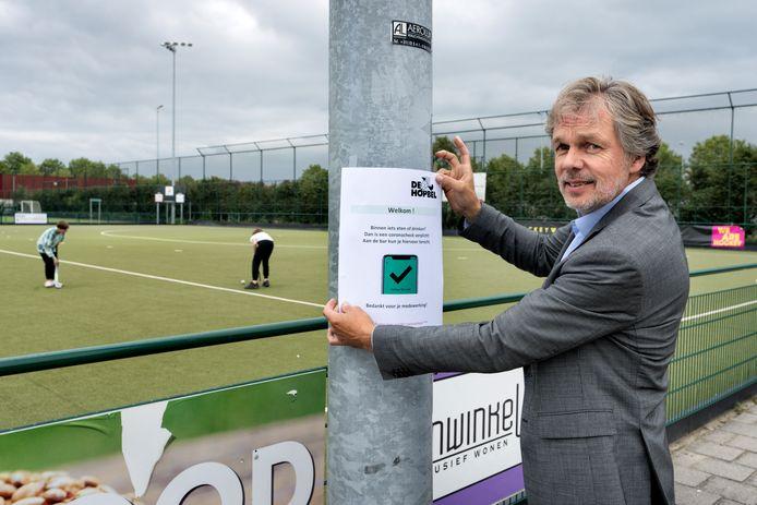 Voorzitter Jos korsten van hockeyclub De Hopbel plakt een coronacheckposter.