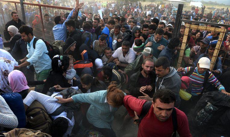 Vluchtelingen breken door een omheining in de Macedonische grensplaats Gevgelija richting Servië.