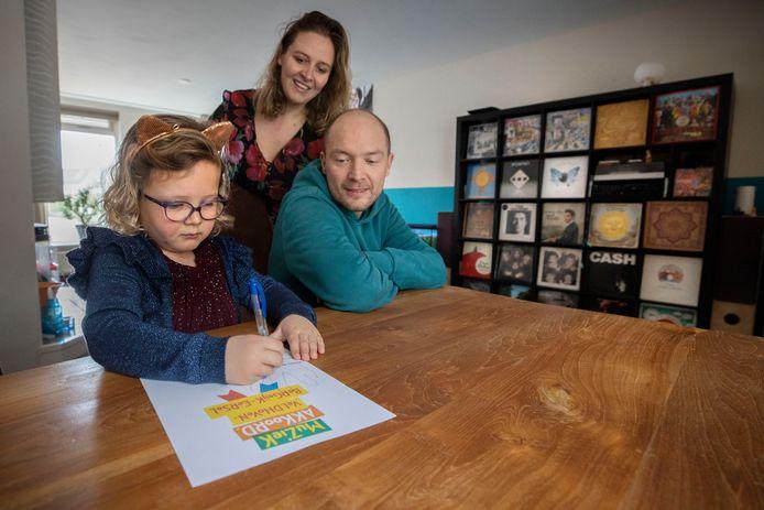Leerling Lizze Tiebosch heeft het muziekakkoord ondertekend. Op de achtergrond kijken ouders Ilse en Niels Tiebosch mee.