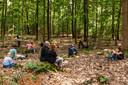 De aanwezigen luisteren in het bos naar Tim Knol