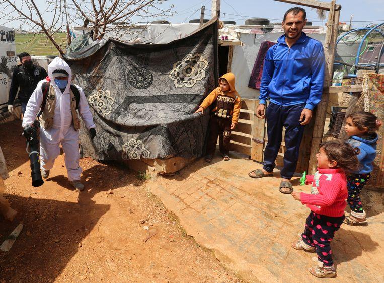 Een vluchtelingenkamp in Libanon wordt gedesinfecteerd.  Beeld REUTERS