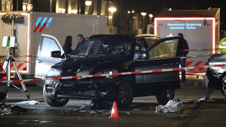De klemgereden auto wordt in de Knokkestraat onderzocht door forensisch medewerkers van de politie. Beeld anp