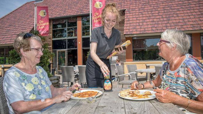 De bezoeksters Wil en Ada genieten van een pannenkoek op het terras van De Schaapskooi in Alphen.