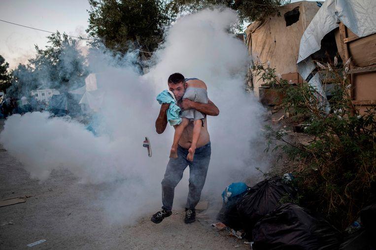 Een man houdt een jongetje vast tijdens een confrontatie met de politie bij het kamp Moria. Die dag, 29 september,  brak er brand uit in het overvolle kamp, waarbij een migrant om het leven kwam. Beeld AFP