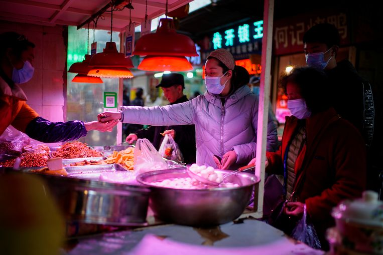 Mensen in de rij voor een voedselverkoper op een straatmarkt in de Chinese stad Wuhan. Beeld REUTERS