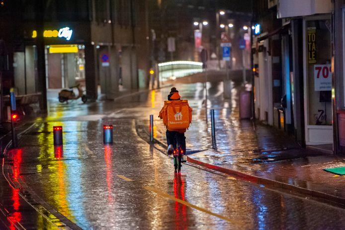 De avondklok is ingegaan. Een fietskoerier in de verlaten Visstraat.
