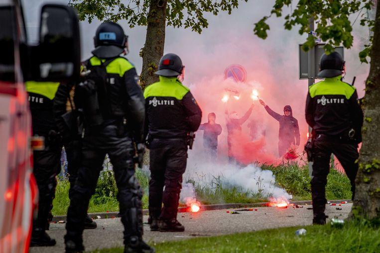 Bij het trainingscomplex van Feyenoord gooiden voetbalfans vuurwerk en stenen naar politieagenten.  Beeld EPA