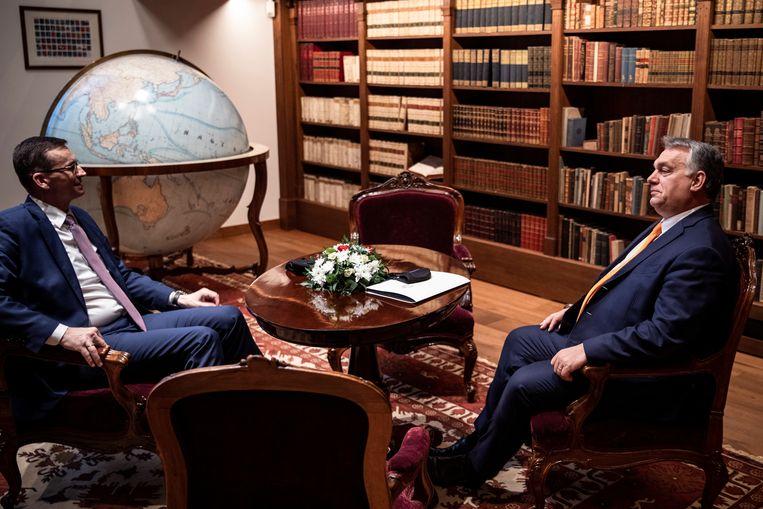 De Poolse premier Morawiecki (links) donderdag in Boedapest in gesprek met zijn Hongaarse collega Orbán. De twee EU-leiders verklaarden hun lot aan elkaar te verbinden. Beeld Reuters