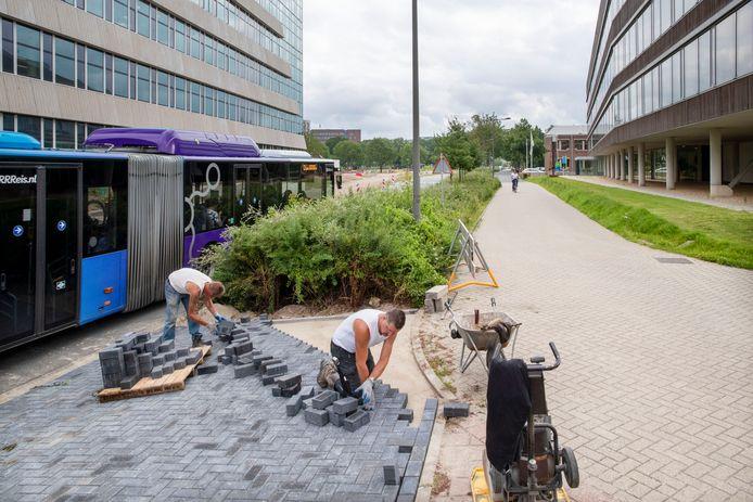 Stratenmakers bezig met het aanleggen van de oversteek over de busbaan naar het nieuwe onderwijsgebouw Aurora. Rechts het Rikilt.