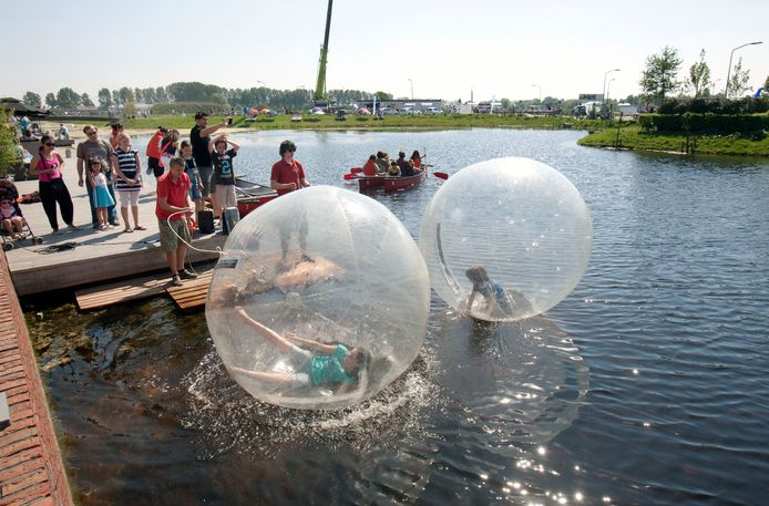 Kinderen vermaken zich uitstekend in een soort luchtbellen in het water in Veenendaal-Oost, archiefbeeld.