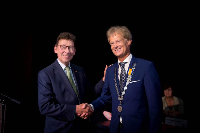 Commisaris van de koning Clemens Cornielje (links) feliciteert Thomas Steenkamp met zijn lintje.