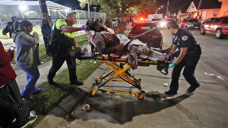 Een gewonde wordt naar een ambulance gebracht. Beeld ap