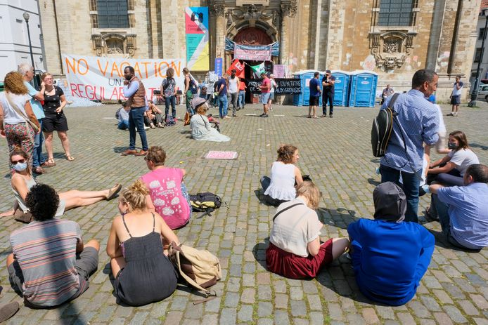 Mensen zitten in stil protest voor de Begijnhofkerk.