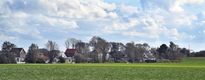 Dijkhuisjes, samengeklonterd tegen de dijk. Rechts de molen van Zonnemaire.
