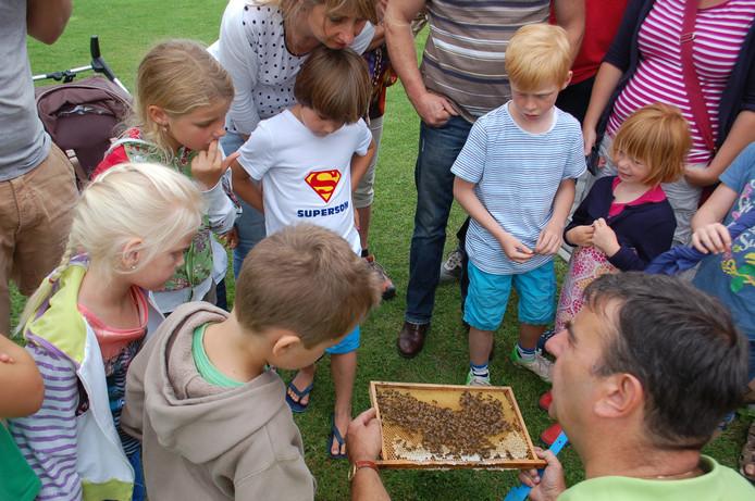 Imker Robert Schuurmans laat kinderen van dichtbij een 'raampje' met bijen zien.