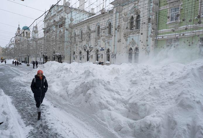 Een vrouw wandelt voorbij een grote berg opzijgeschoven sneeuw in centraal Moskou. Beelden van vandaag.