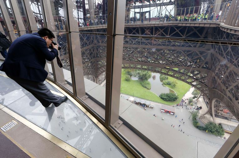 A visitor takes pictures as he stands on the new glass floor at the Eiffel Tower in Paris October 6, 2014. The Eiffel Tower inaugurated on Monday a new solid glass floor that  allows visitors to have bird's eye view from 57 metres above the ground. The new attraction is part of the first floor renovation at the Eiffel tower to attract more tourists.  REUTERS/Jacky Naegelen  (FRANCE - Tags: TRAVEL SOCIETY) Beeld Reuters