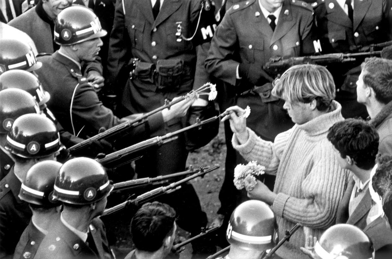 De Amerikaan George Harris steekt anjers in de geweerlopen van politiemannen tijdens een anti-oorlogsprotest in 1967. Beeld The Washington Post via Getty Im