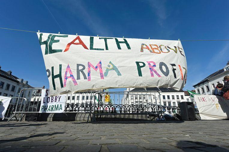 Een spandoek tegen grof geldgewin binnen farma-industrie in Brussel. Beeld Photo News