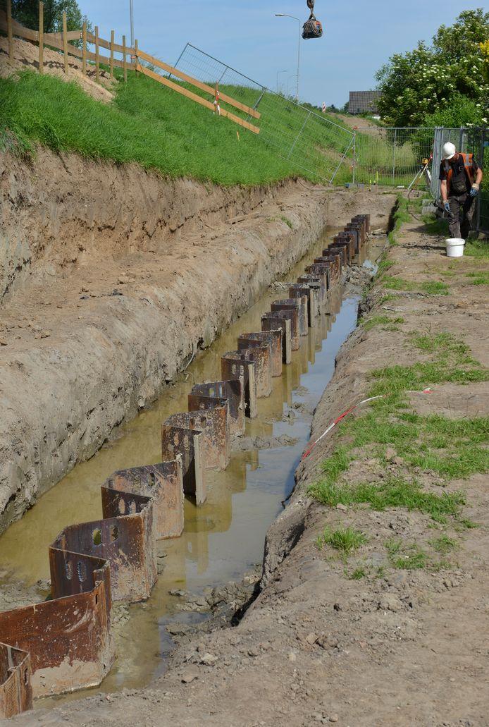 Een damwandscherm diep in de klei onderaan een dijk, hier in Opheusden