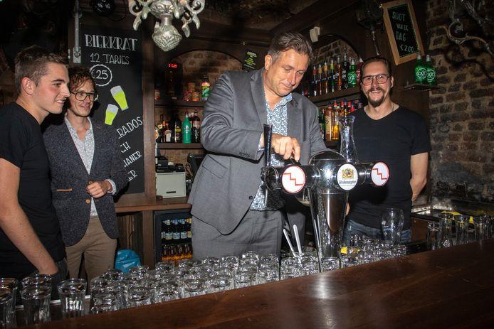 Wethouder Cees Pille tapt het eerste biertje in Feestcafé De Kelder met de twee nieuwe eigenaren. Patrick Kint staat rechts op de foto en Jonathan staat links naast Pille. Een barmedewerker kijkt toe.