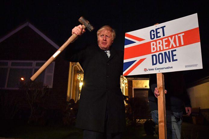 De Britse premier Johnson hamert in aanloop naar de verkiezingen een bordje met de tekst 'Get Brexit Done, stem Conservatief' in de tuin van een supporter de grond in.