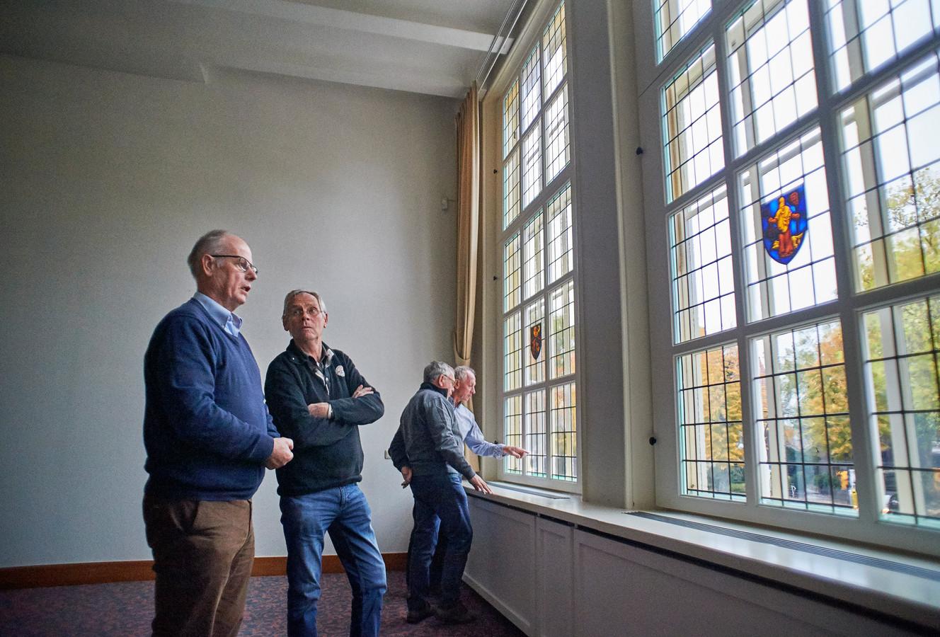 Leden van de heemkundekring vlnr Christ van Bree, Marius Strijbosch, Henk Bolwerk en Ad Jansen bij de glas-in-lood-ramen in het raadhuis te Erp.