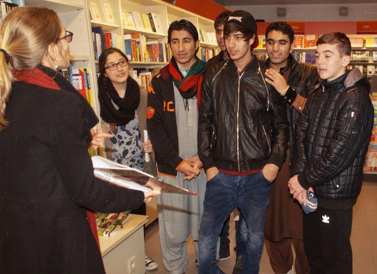 Een groep vluchtelingen uit opvangcentrum Westakkers leert het Nederlands in een boekenwinkel.
