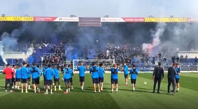 De PEC-spelers kijken aandachtig naar het vuurwerk van de fans.