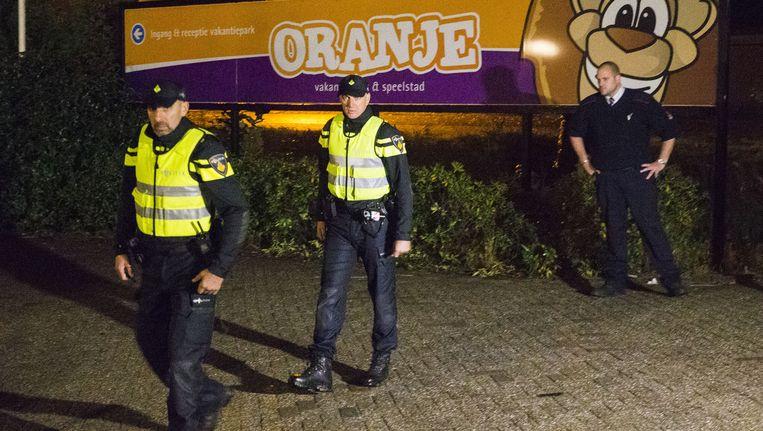 Politieagenten en een beveiliger bij de toegang naar het vakantiepark in Oranje waar asielzoekers worden opgevangen Beeld anp