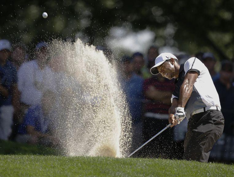 Tiger Woods ploegt door een bunker op hole 17 tijdens zijn derde ronde bij de PGA Championship. Beeld ap