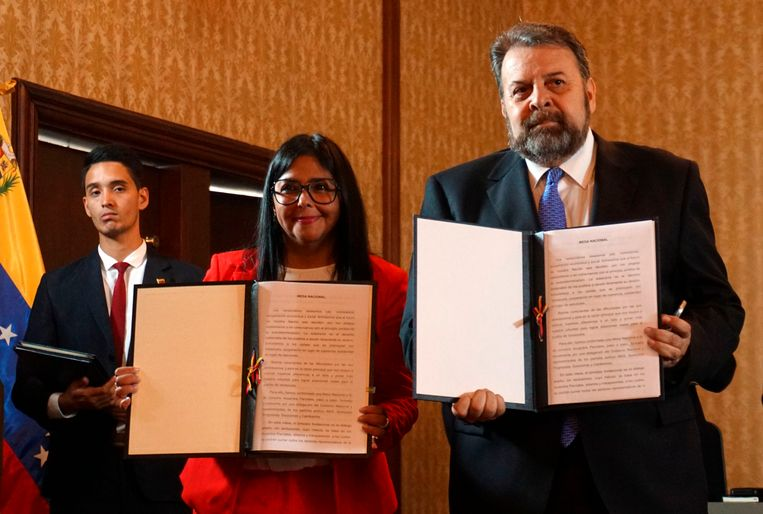 Vicepresident Delcy Rodriguez (midden) en oppositielid Timoteo Zambrano tonen het akkoord dat op 16 september is ondertekend. Beeld AFP