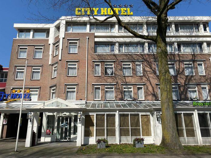 Het City Hotel in Oss. De ramen van het  restaurant zijn nog afgeplakt met plastic. Het hotel huisvest nu arbeidsmigranten.