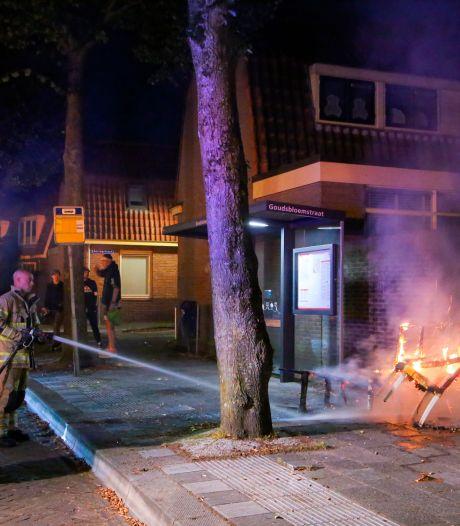Buurtbewoners proberen met emmers water brandende stoelen bij bushokje te blussen