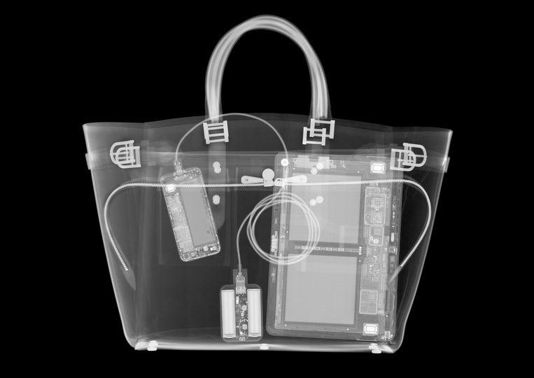 Een röntgenfoto van een handtas vol elektronische apparatuur. Beeld Getty Images/Science Photo Libra