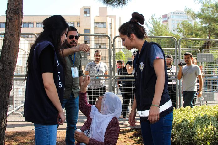 Een Turkse vrouw zit voor de ingang van het gemeenschapshuis in Diyarbakir uit protest tegen het afzetten van de burgemeester van de stad.