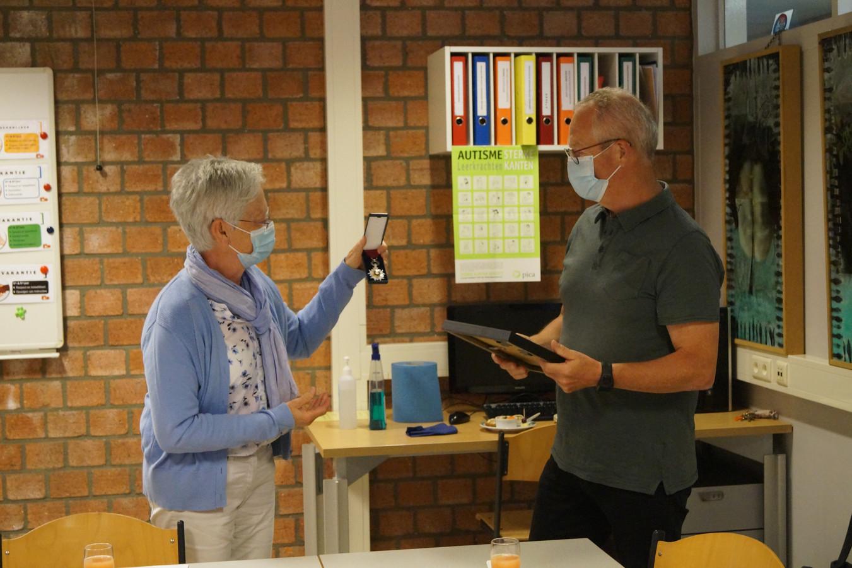 Betty De Mûelenaers, voorzitter van de scholengroep, overhandigt het ereteken aan Ronny De Craemer