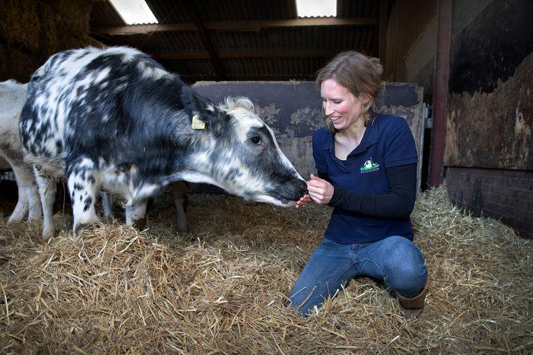 Boerin Ilse Antonissen in het stro met een van haar dieren. Beeld Ton Toemen