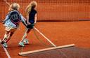 Na het tennissen wordt uiteraard netjes de baan geveegd.