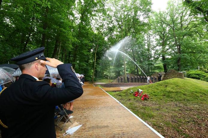 Een brandweerman brengt het ere-groet terwijl op de achtergrond het water-ereteken in werking is gezet.