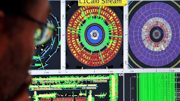 In het CERN-laboratorium in Genève tonen computerschermen wat er in de nieuwe LHC-deeltjesversneller gebeurt. © EPA Beeld