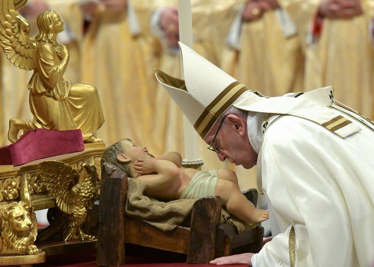 Paus Franciscus kust het beeld van het kindje Jezus bij aanvang van de kerstnachtmis in de Sint-Pieter in Rome.