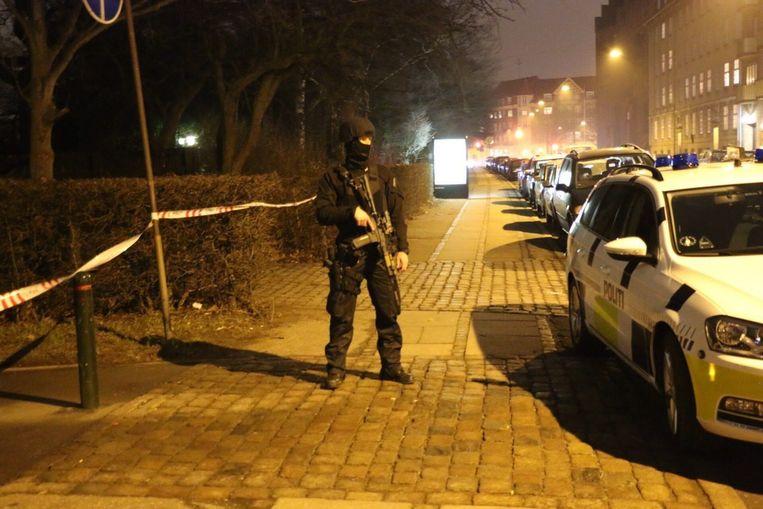 Een zwaar bewapende agent houdt de wacht op straat in Kopenhagen. Beeld epa