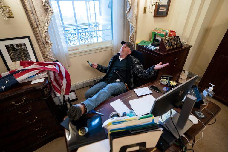 Richard Barnett met zijn schoenen op het bureau van Nancy Pelosi. Beeld EPA